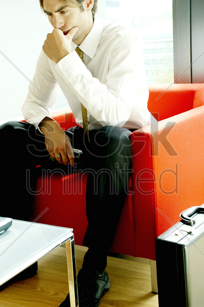 businessman sitting on a sofa thinking stock photo