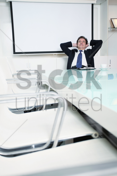 businessman sitting on office chair with hands behind head stock photo