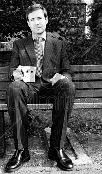 businessman sitting on the bench holding a cup of coffee stock photo