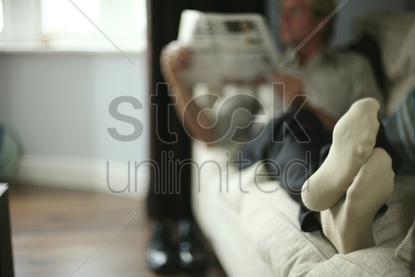 businessman sitting on the couch reading newspaper with the focus on his socks stock photo