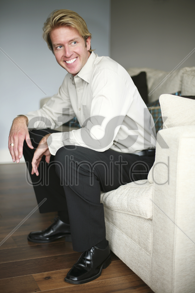 businessman sitting on the couch smiling stock photo