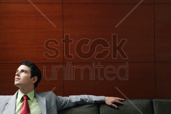 businessman sitting on the couch thinking stock photo