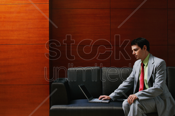 businessman sitting on the couch using laptop stock photo