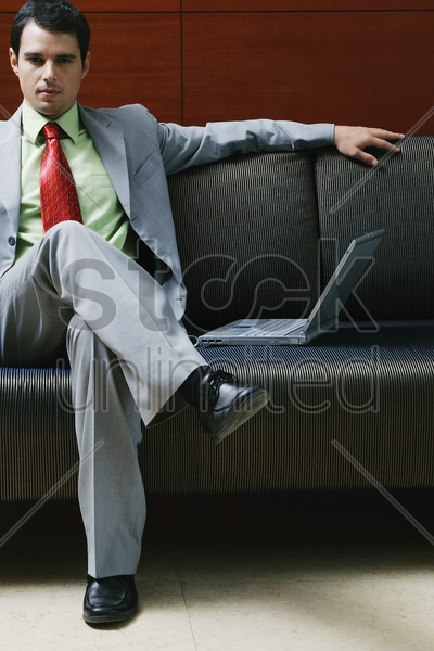 businessman sitting on the couch with a laptop beside him stock photo