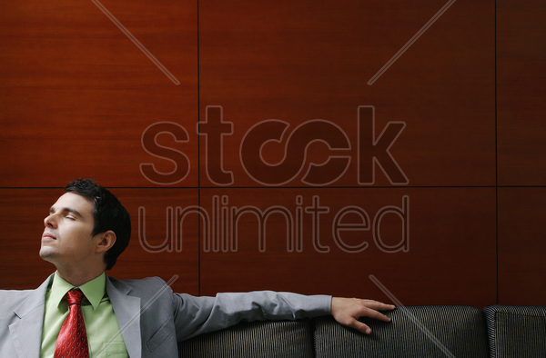 businessman sitting on the couch with his eyes closed stock photo