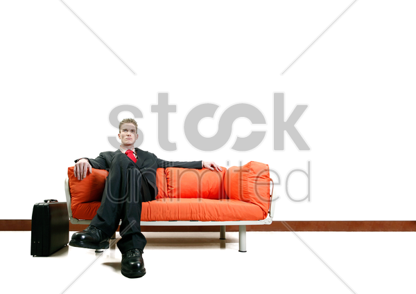 businessman sitting on the couch with his legs crossed stock photo