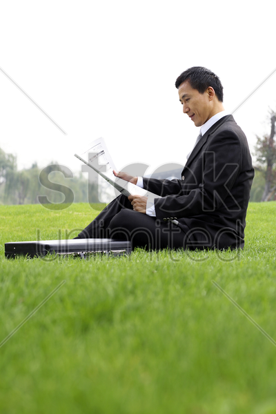 businessman sitting on the field reading newspaper stock photo