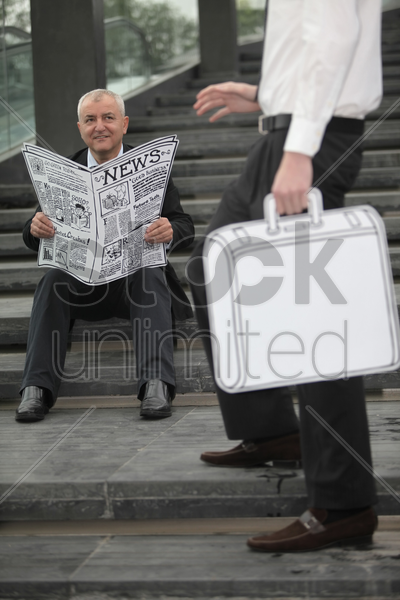 businessman sitting on the stairs reading newspaper stock photo