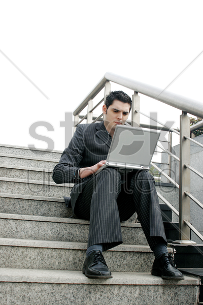 businessman sitting on the stairs using laptop stock photo
