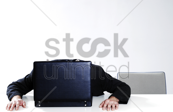 businessman sleeping on an opened briefcase stock photo