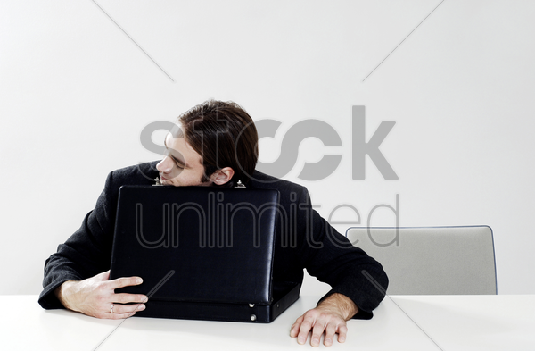 businessman sleeping on briefcase stock photo