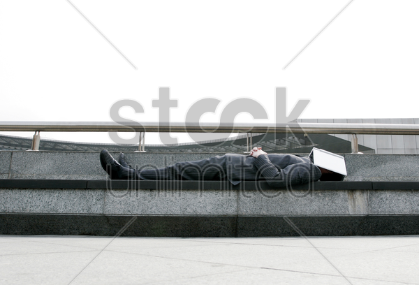 businessman sleeping on the bench with a book covering his face stock photo