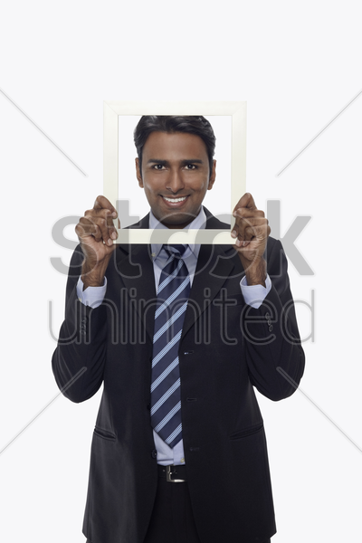 businessman smiling and looking through cutout paper frame stock photo