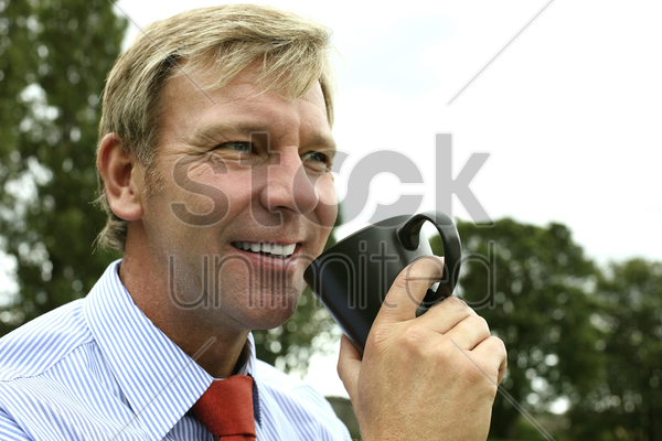 businessman smiling while holding a cup stock photo
