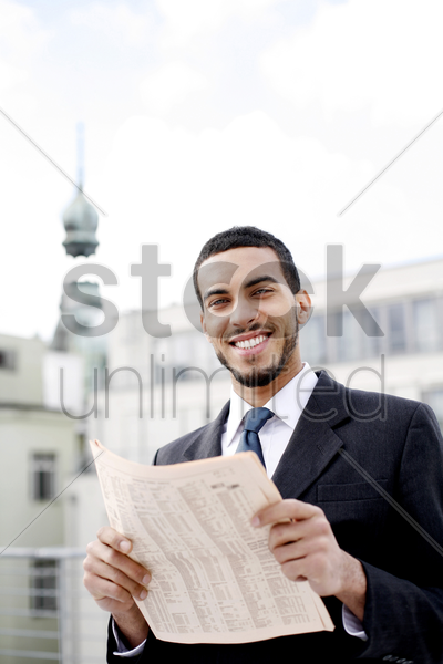 businessman smiling while holding a newspaper stock photo