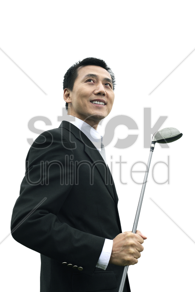 businessman smiling while holding golf club stock photo