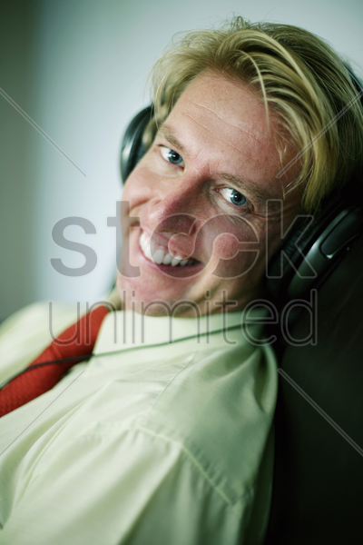 businessman smiling while listening to music on the headphones stock photo