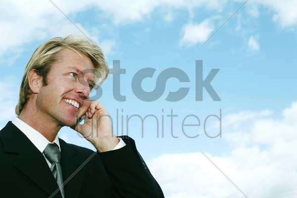 businessman smiling while talking on the phone stock photo