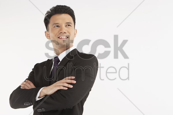 businessman smiling with arms crossed stock photo