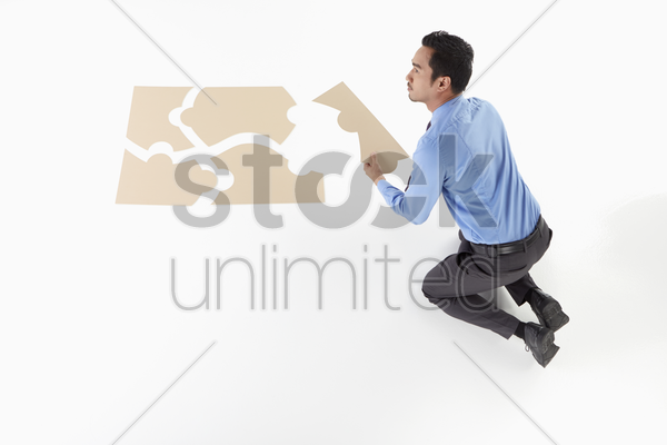 businessman solving a puzzle stock photo