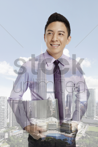 businessman standing against a cityscape background stock photo