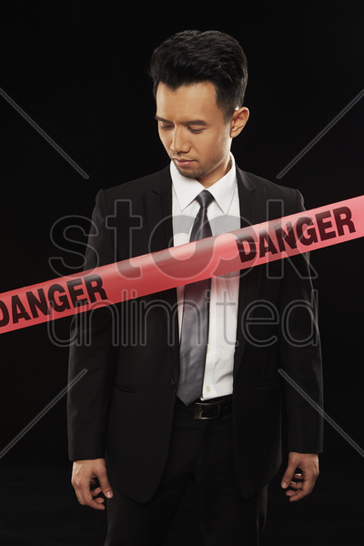 businessman standing behind a 'danger' tape stock photo