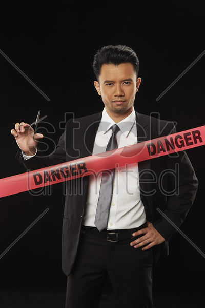 businessman standing behind 'danger' tape, holding scissors stock photo
