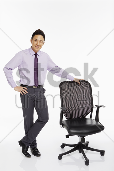 businessman standing beside a chair stock photo
