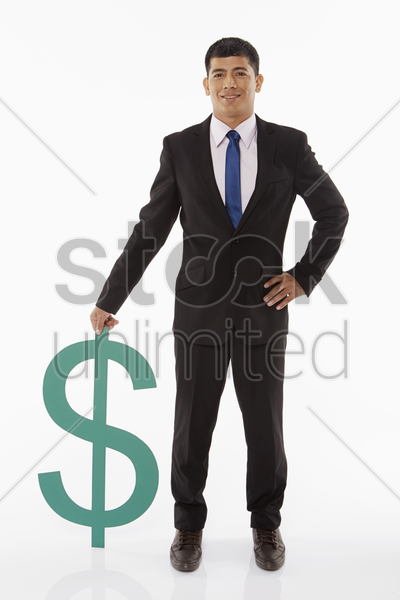 businessman standing beside a dollar sign stock photo