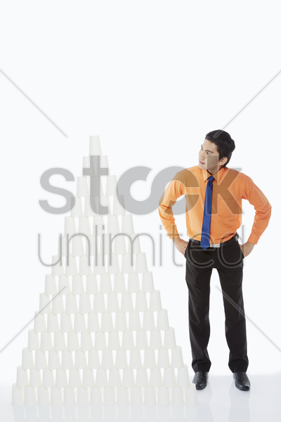 businessman standing beside a pyramid of disposable cups stock photo