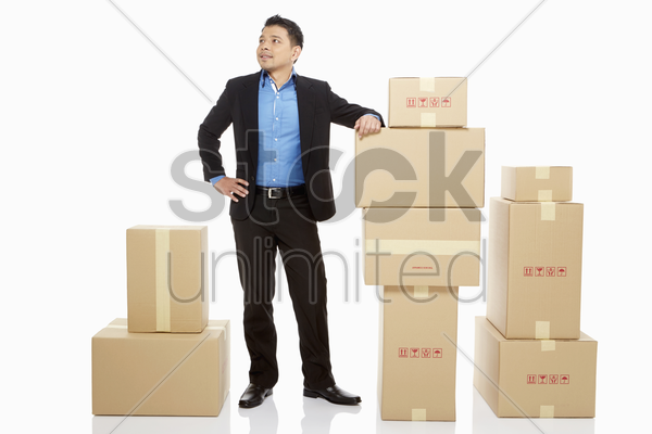 businessman standing beside a stack of cardboard boxes stock photo