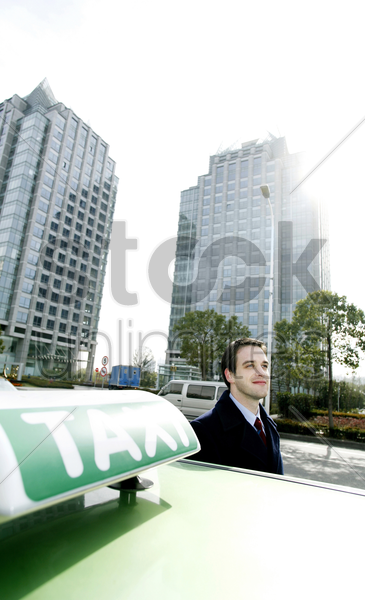 businessman standing beside a taxi stock photo