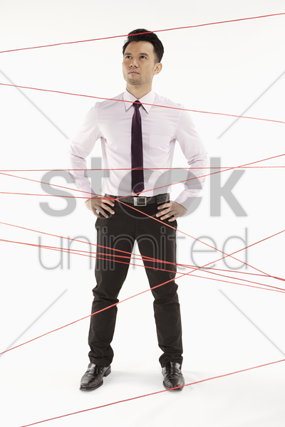 businessman standing in between tangled wires stock photo