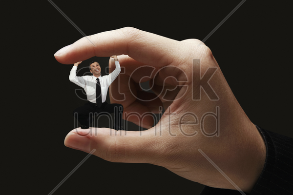 businessman standing in between two fingers stock photo