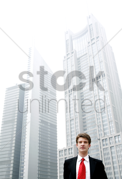 businessman standing in front of tall buildings stock photo