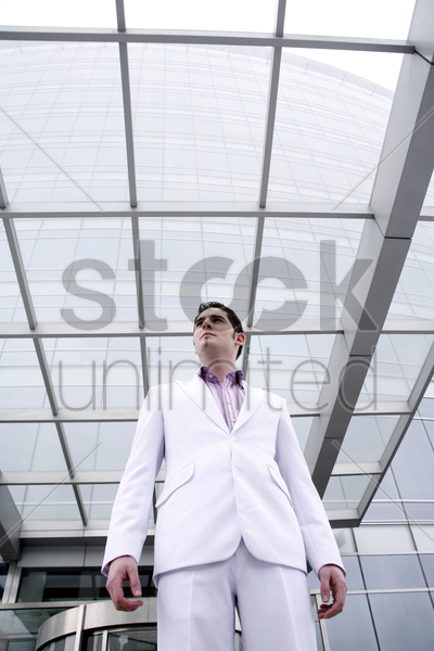 businessman standing in front of the office building stock photo