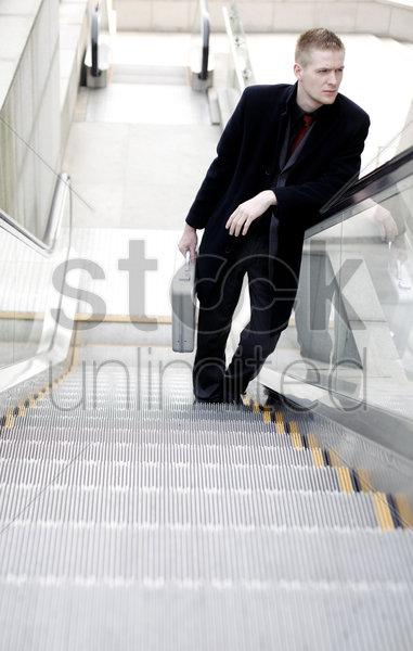 businessman standing on an escalator stock photo