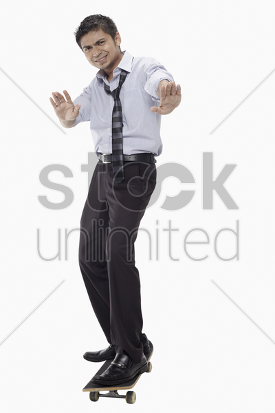 businessman standing on skateboard stock photo