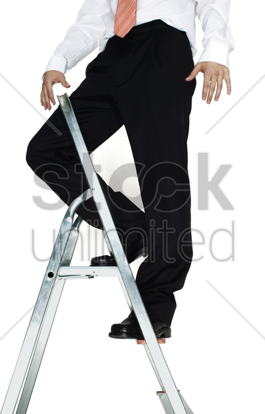 businessman standing on top of a ladder stock photo