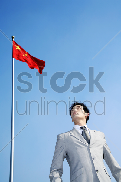 businessman standing under a flag stock photo