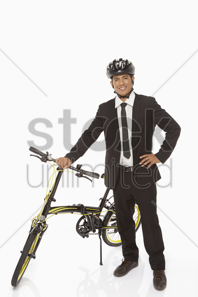 businessman standing with a bicycle stock photo