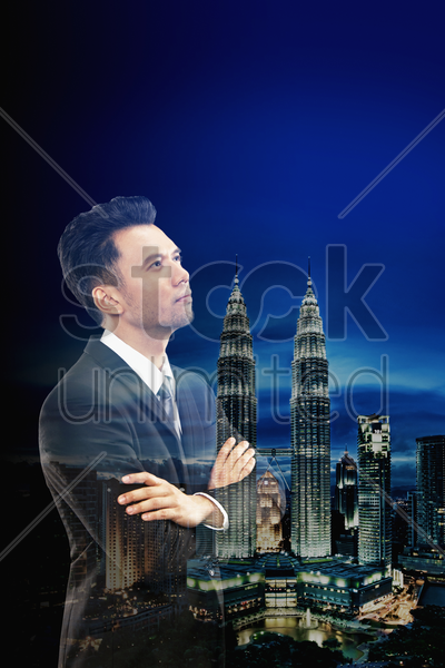 businessman standing with arms crossed against a cityscape background stock photo