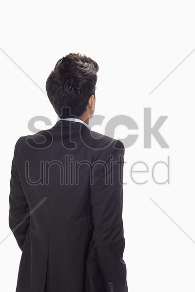 businessman standing with back facing the camera stock photo