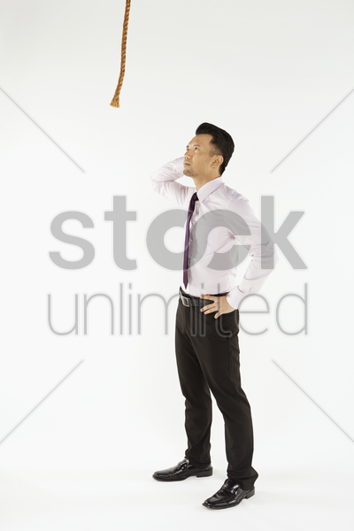 businessman staring at a rope, contemplating stock photo