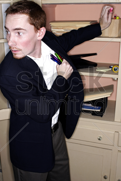 businessman stealing stationery from his office stock photo