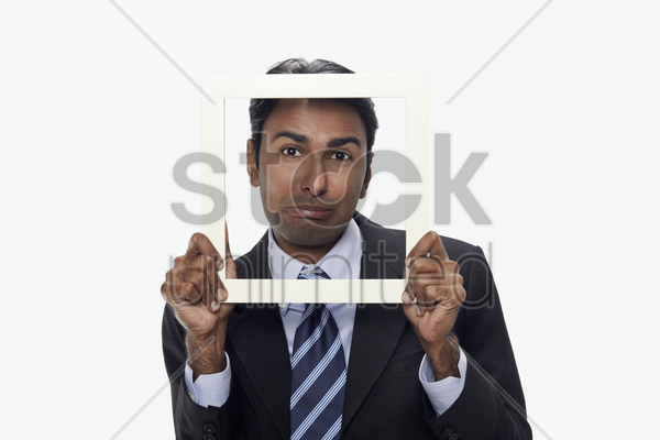 businessman sulking and looking through cutout paper frame stock photo