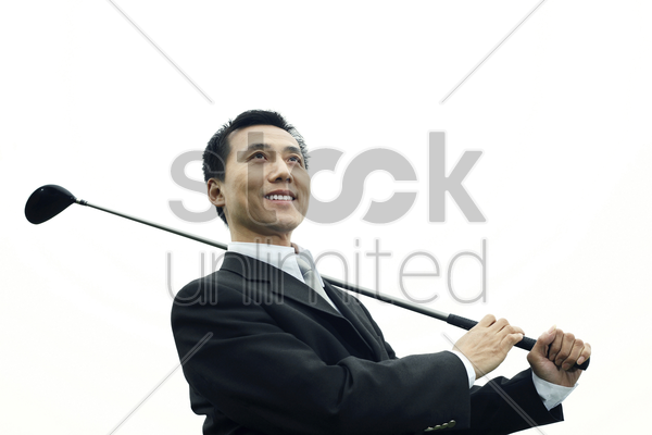 businessman swinging golf club stock photo