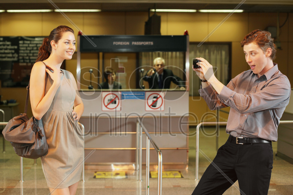 businessman taking a picture of businesswoman using mobile phone, airline check-in attendant pointing at them stock photo
