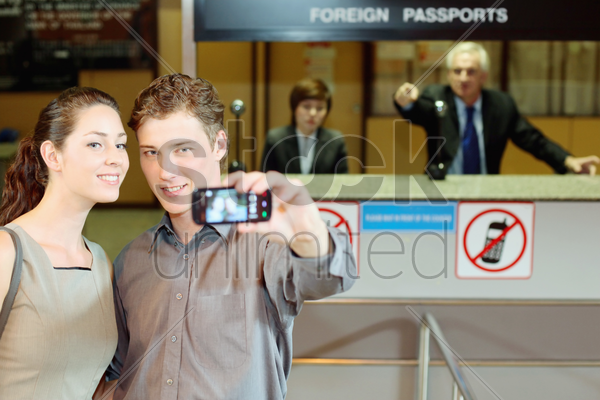 businessman taking a picture using mobile phone, airline check-in attendant pointing at them stock photo