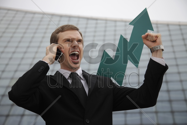 businessman talking on mobile phone showing fist with an arrow pointing up in the background stock photo